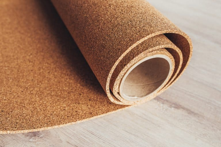 Cork roll being laid out in a floor for finishing, How To Soundproof Your Apartment Floor [10 Proven Methods]