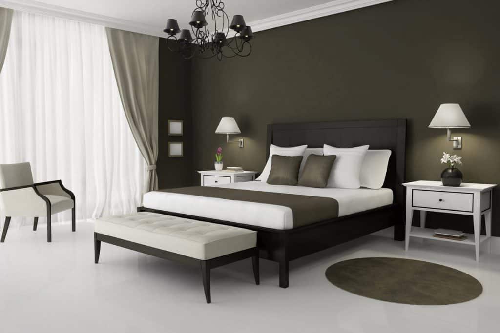 Yatakta beyaz nevresimlerle oturma odasında koyu yeşil boyalı duvar