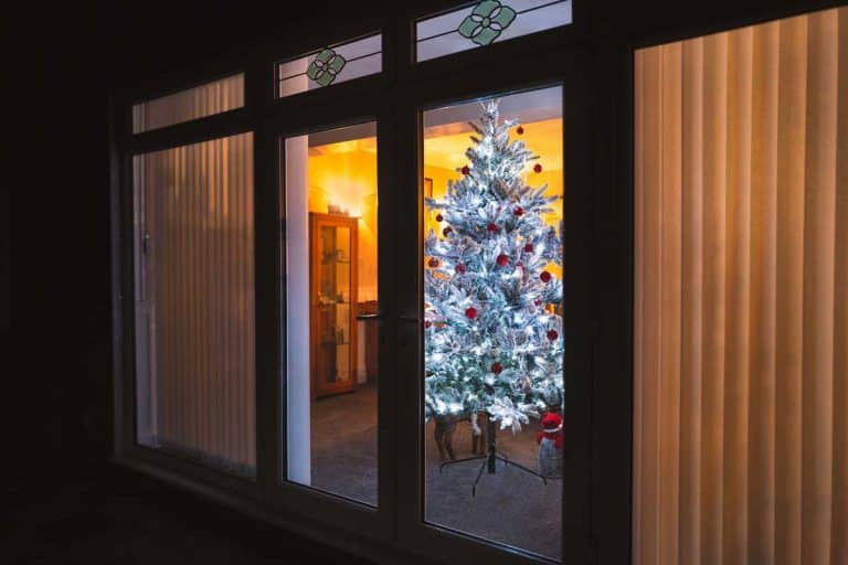 A frosted white artificial christmas tree with red and silver decorations seen through large french doors with vertical slat blinds, Can You Put Blinds On French Doors? (And How To)