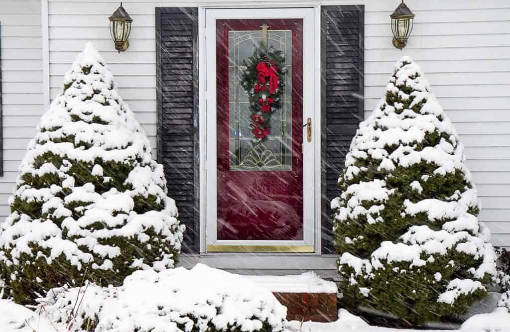 A house with red door during a winter storm