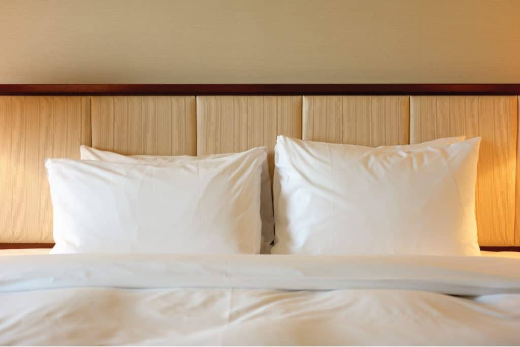 A king-size luxury hotel bed with four pillows