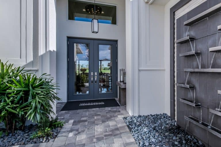 A large modern contemporary mansion with a gray steel framed glass French door, 8 Types of Patio Doors