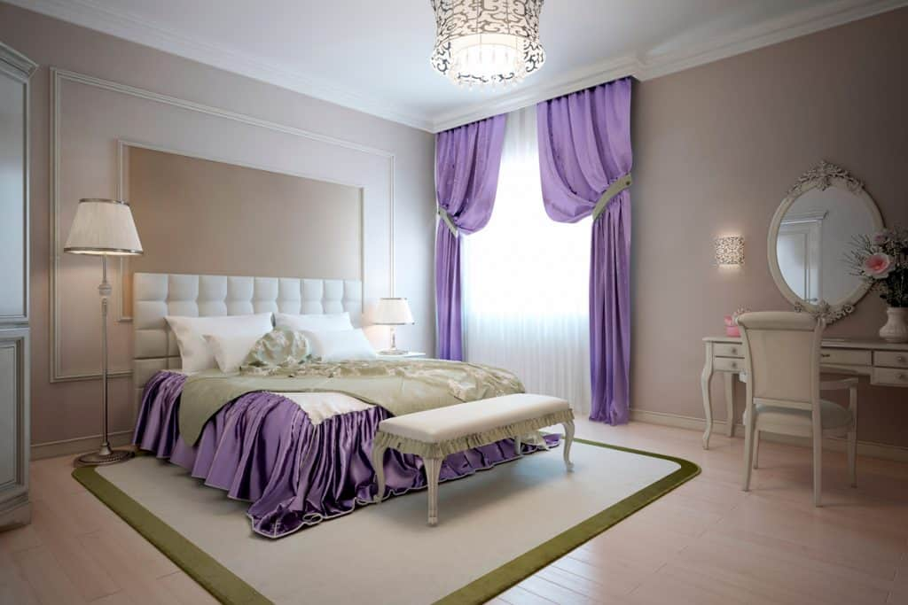 A luxurious huge bedroom with purple curtains and a bed with purple beddings matched with walls painted in beige