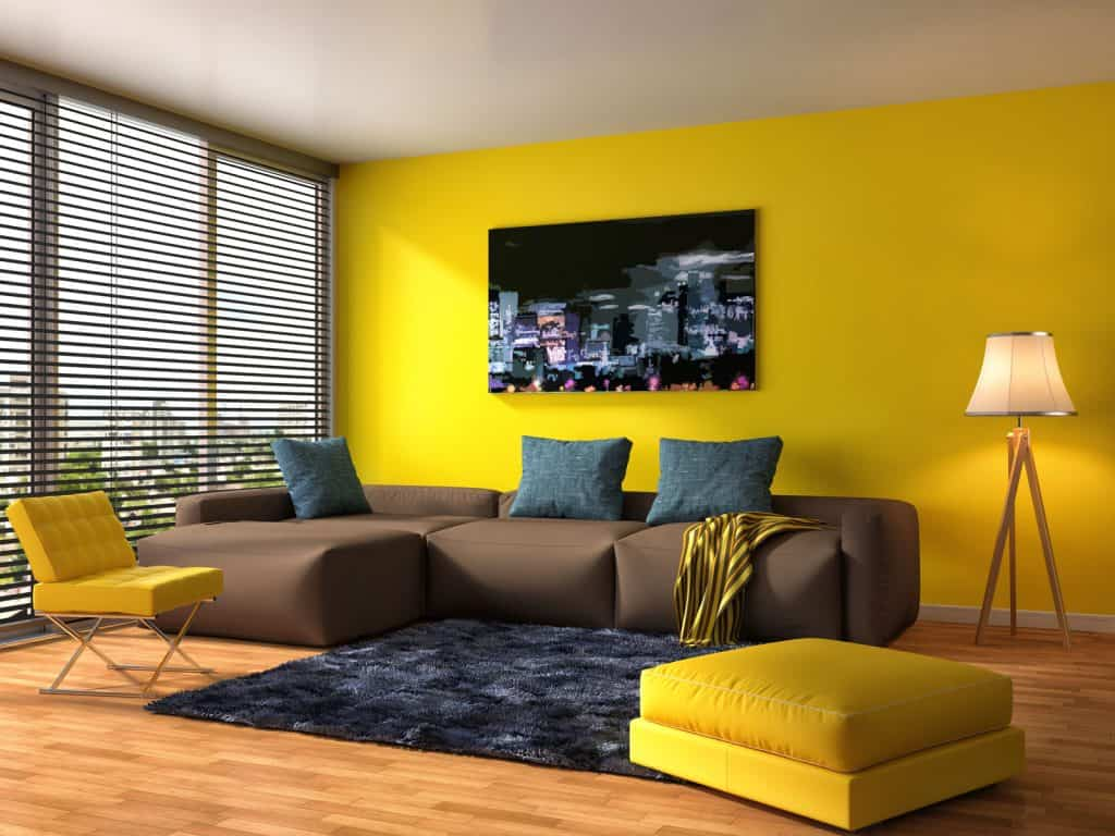 A luxury living room showing a huge couch and yellow accent wall