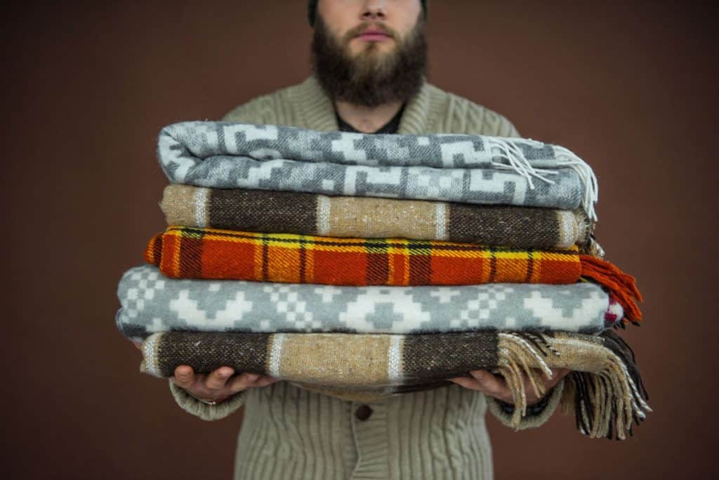 A man holding a pile of blankets