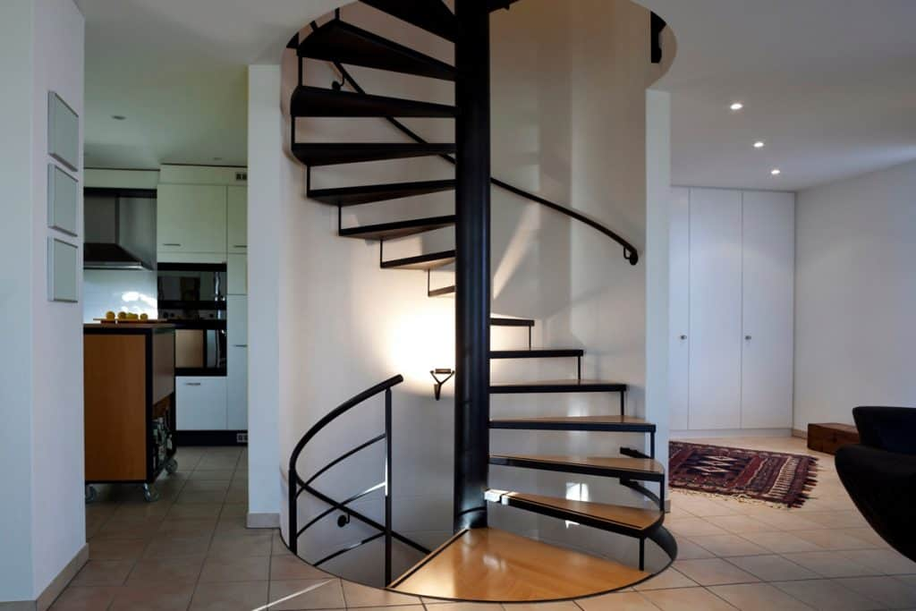 A metal framed wooden spiral staircase with a metal centerpole