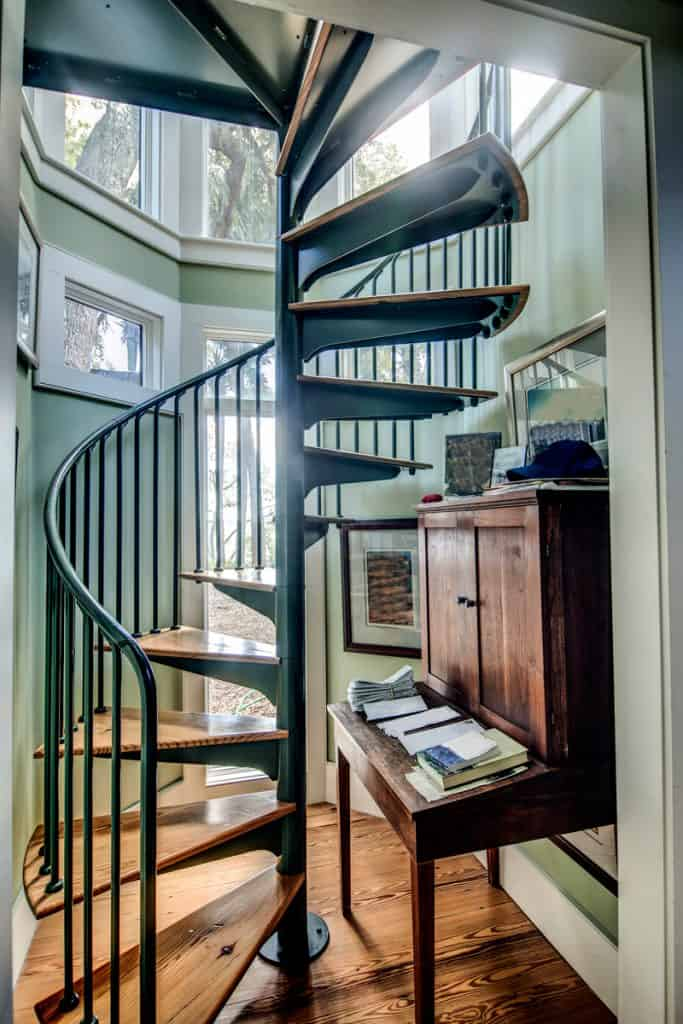 A metal framed wooden stepped staircase in a class themed house