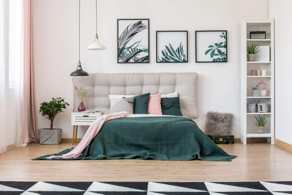A modern bedroom with beige colored walls and dark green colored beddings