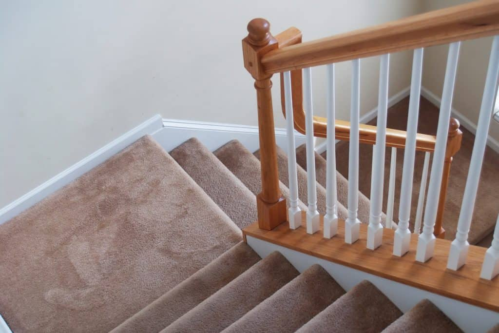 A modern house with a carpet staircase and a stair spindle colored with a combination of white and brown