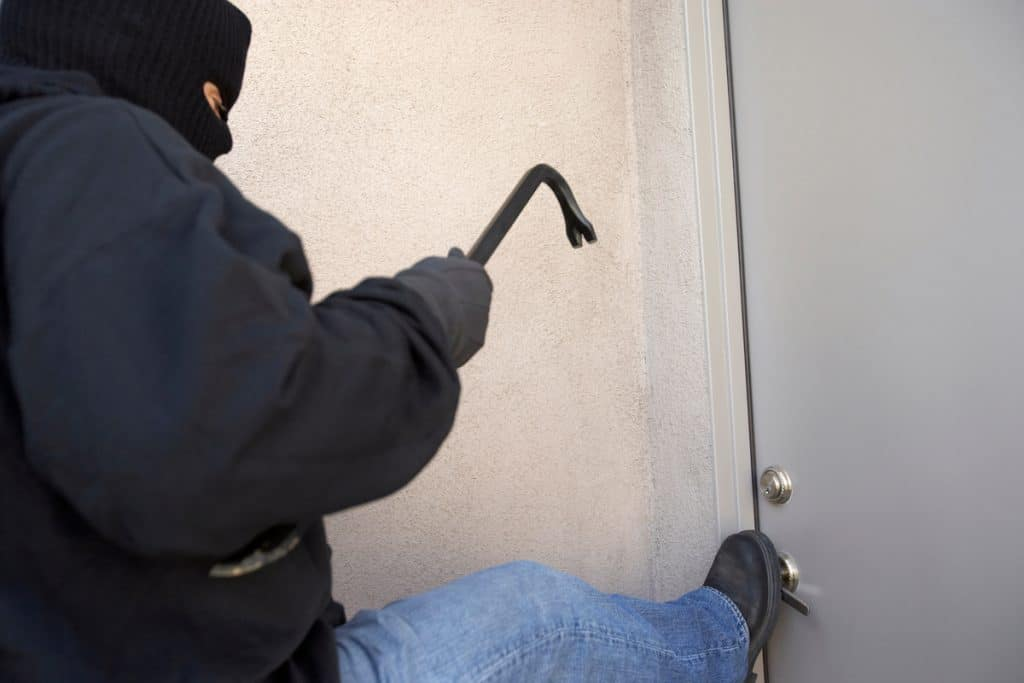 A robber holding a crowbar and kicking the door trying to bust in and rob the house