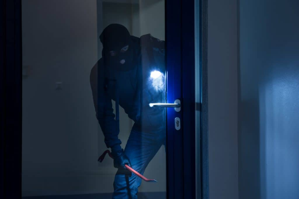 A robber holding a flashlight and a crowbar looking behind the glass door