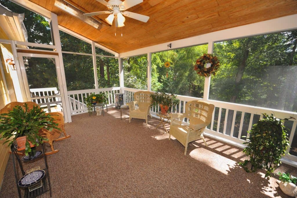 A-screened-in-porch-with-plants-and-chairs-for-featured, How To Cover Porch Windows? 6 Awesome Ideas!