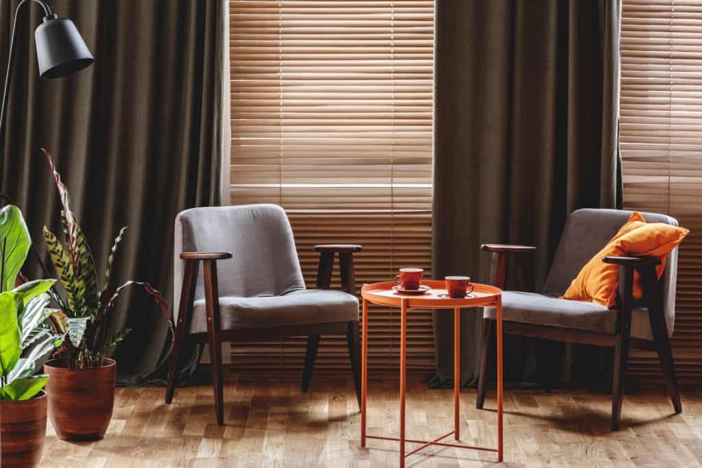 İki küçük sandalyeli küçük bir kahve alanı, küçük bir sehpa ve arka planda gölgelikler