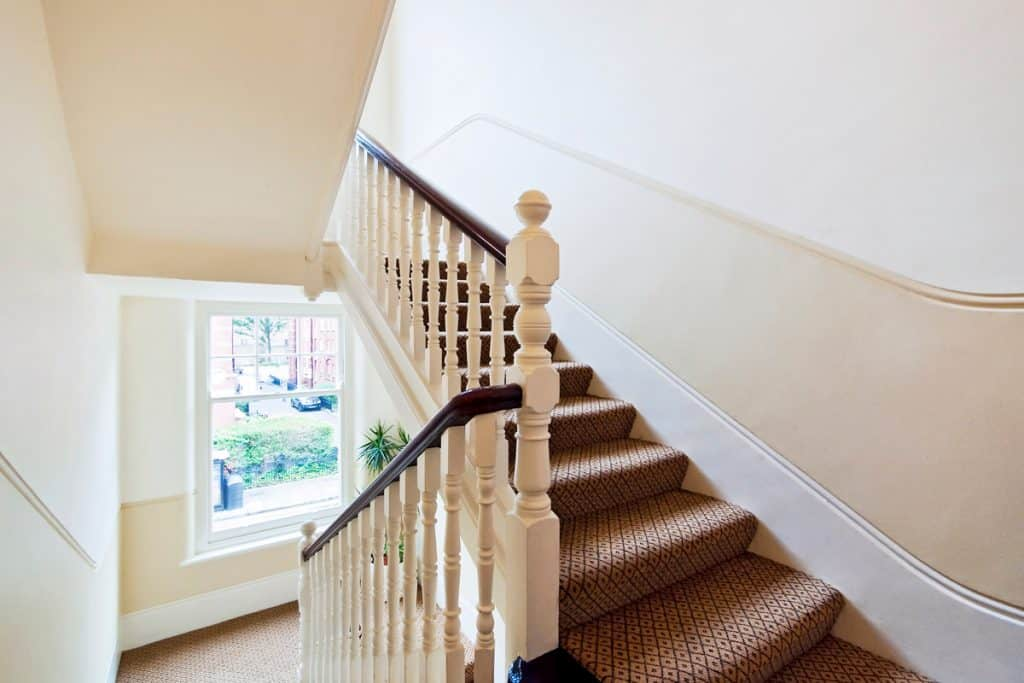 A staircase with a brown carpet attachment and a beige colored stair spindle