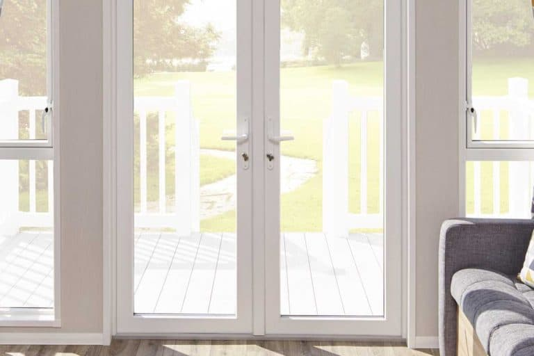 A white french door entrance to a living room with view of the front yard, How to Hang Roman Shades on French Doors [5 Steps]
