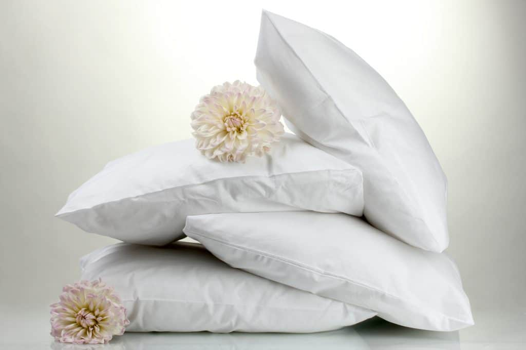 Four white pillows with flowers placed on top and the side