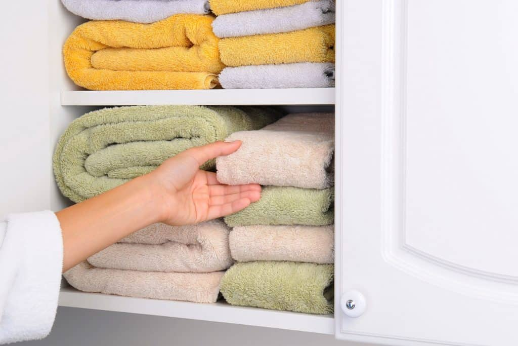 A woman picking out a towel in a white cabinet