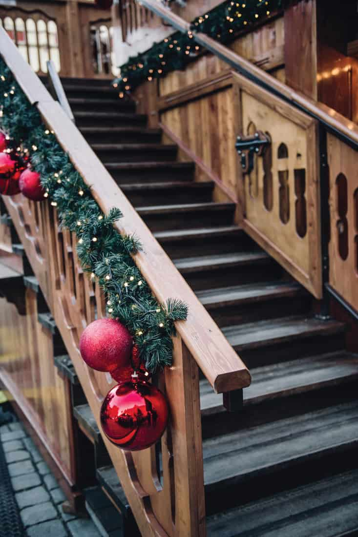 A wooden staircase is decorated for Christmas which leads to the house of Santa Claus