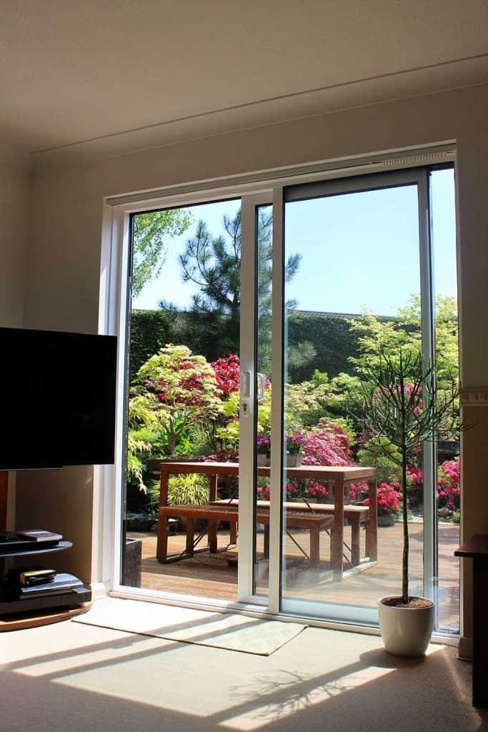 Aluminium patio doors overlooking back garden with decking
