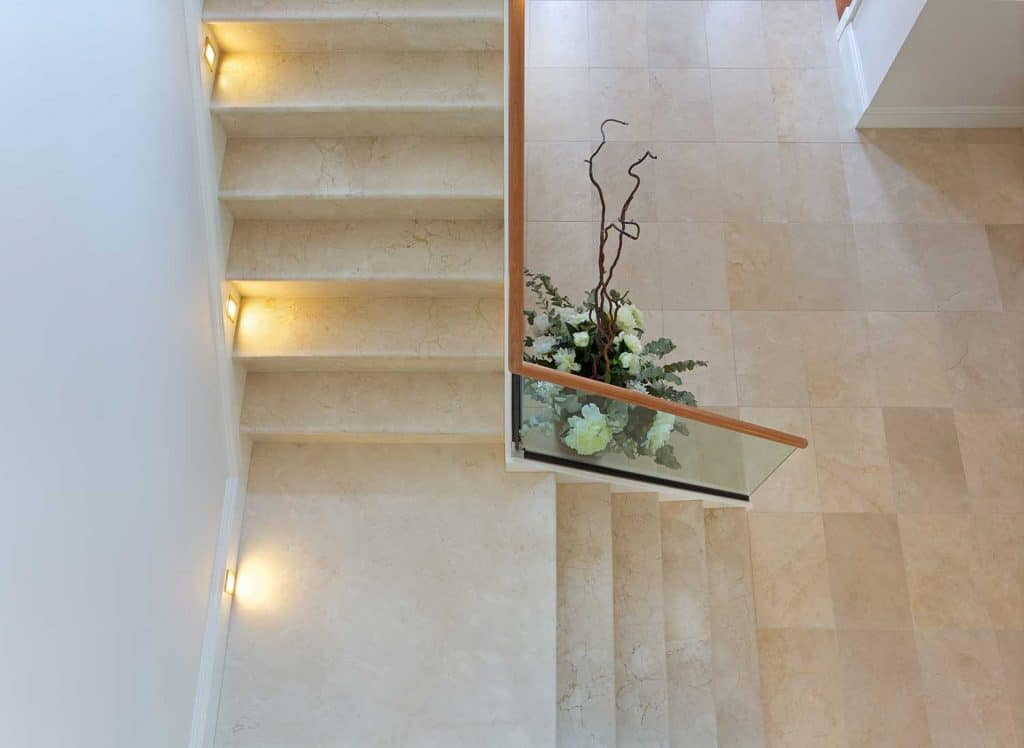 An overhead view of a hallway in a luxury home with expensive Italian marble tile flooring and stairs