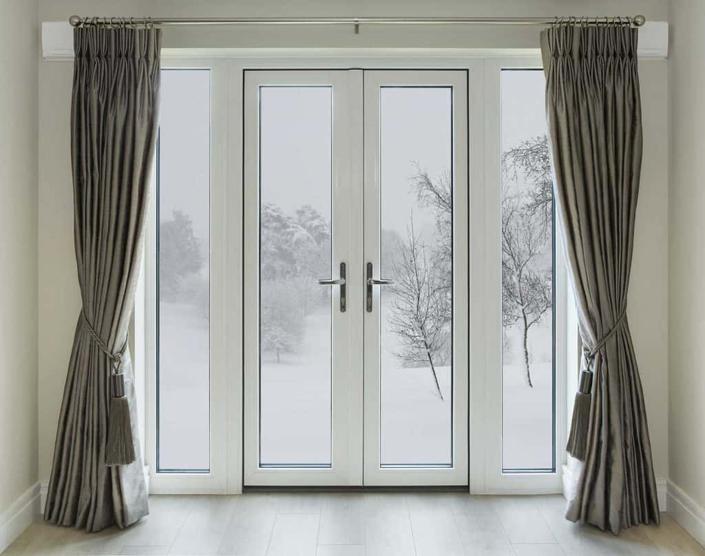 Beautifully crafted white double glazed French doors in a luxury home with winter view