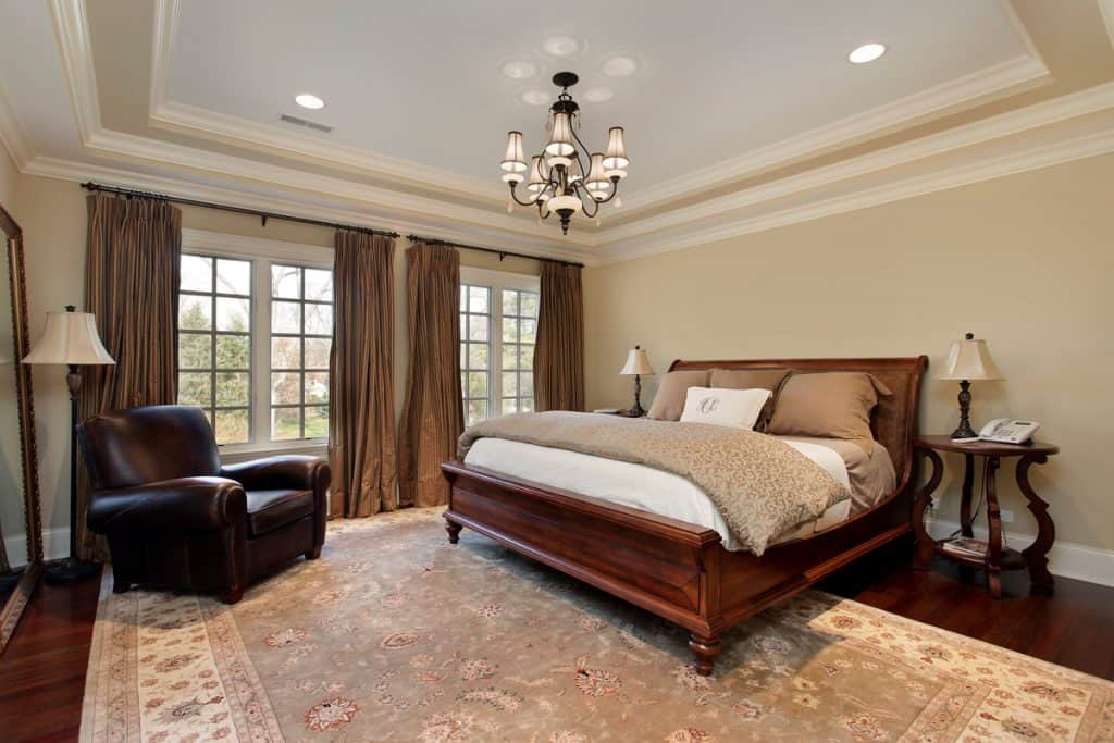 Classic bedroom with a king sized bed and a window with huge brown curtains
