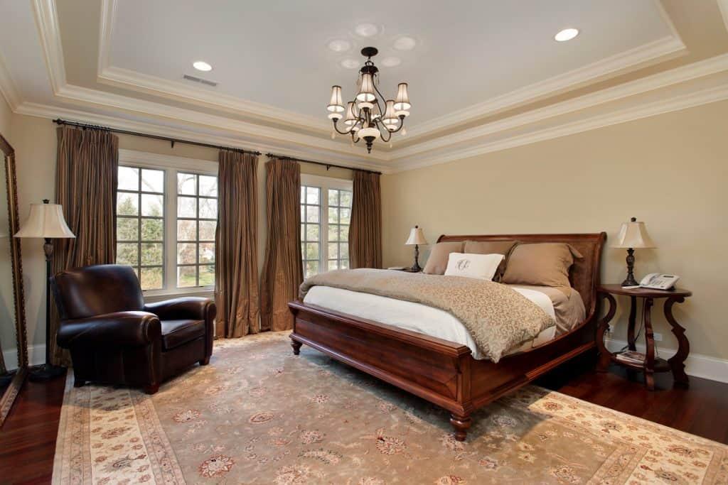 Bir kral yatak ve büyük kahverengi perdeli bir pencere bulunan klasik yatak odası