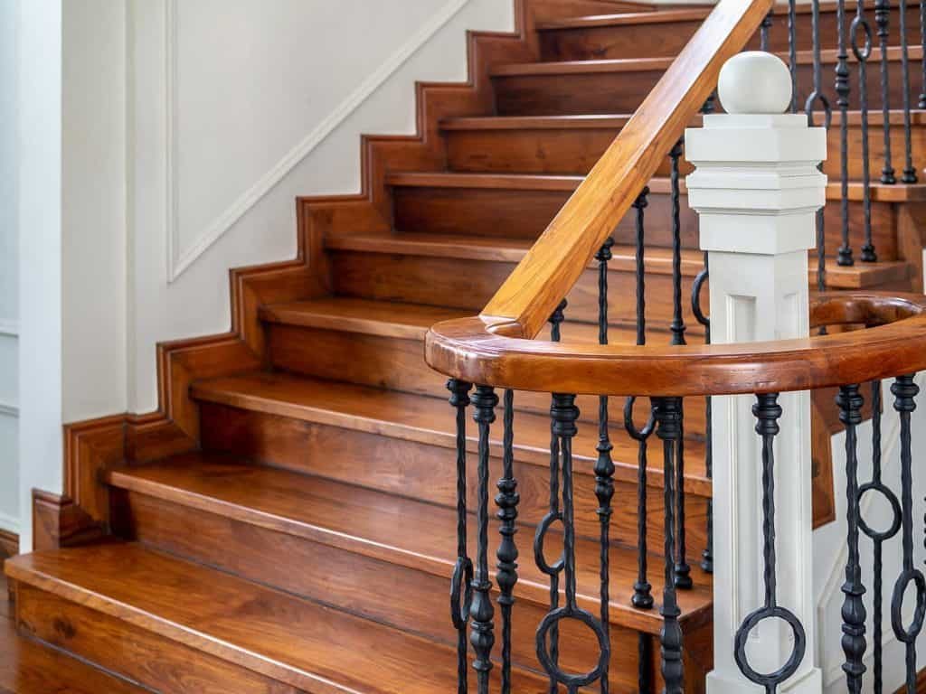 Classic vintage elegant wooden staircase with wrought iron railing
