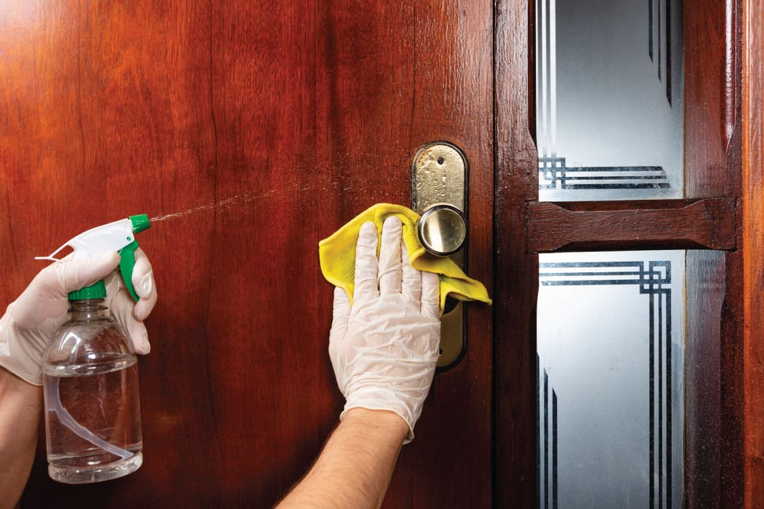 Cleaning wooden door handle during pandemic covid-19