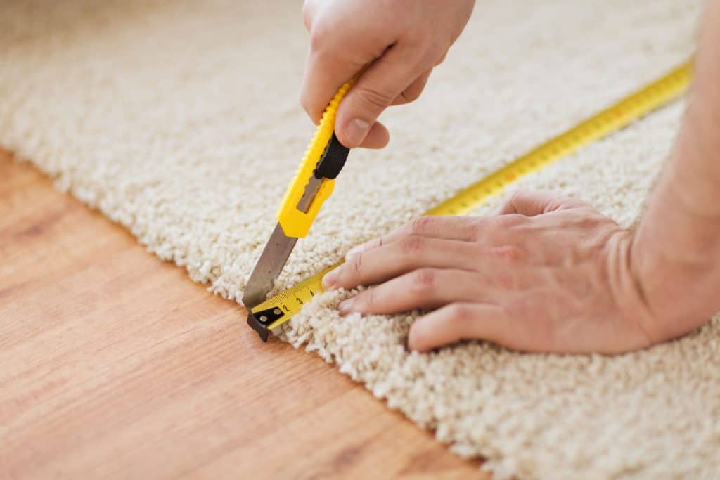Close up of male hands cutting a carpet with cutter and a steel tape