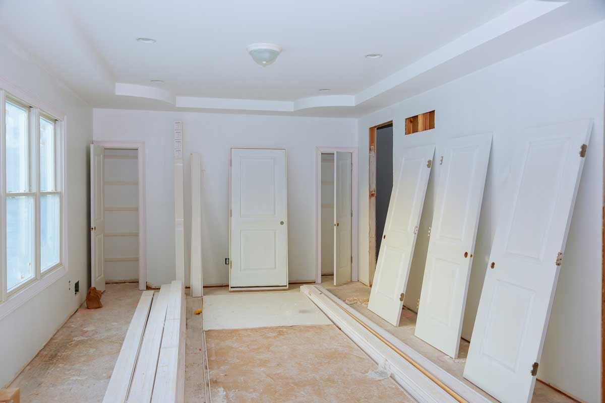 Handyman installing door with an mounting foam in a room