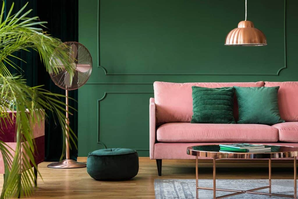 Copper lamp and table in a green living room interior