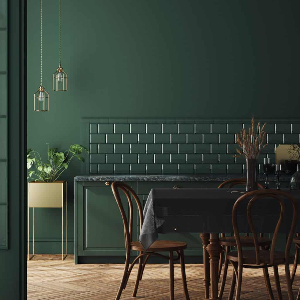 Dark green themed dining area with dark ratan dining chairs and a table with blanket