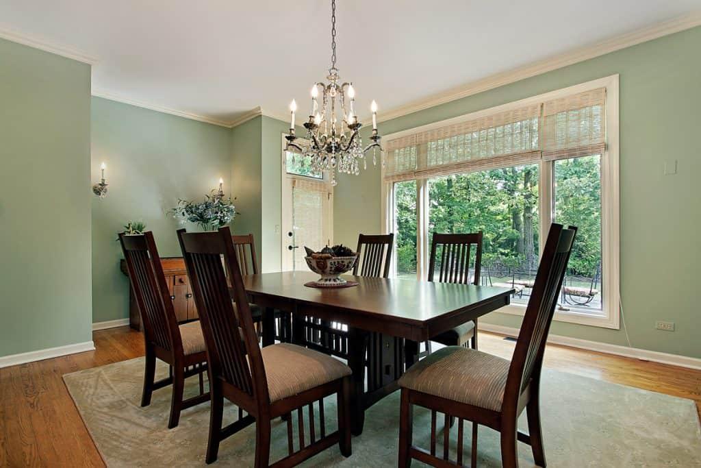 Koyu boyalı yemek sandalyeleri ve opak yeşil boyalı duvarda antika mum aydınlatmalı avize ile masa