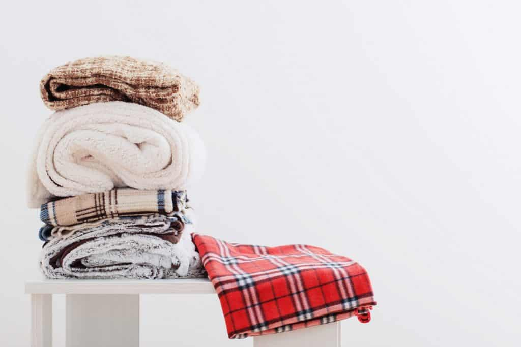Different kinds of blankets folded and placed on top of a table