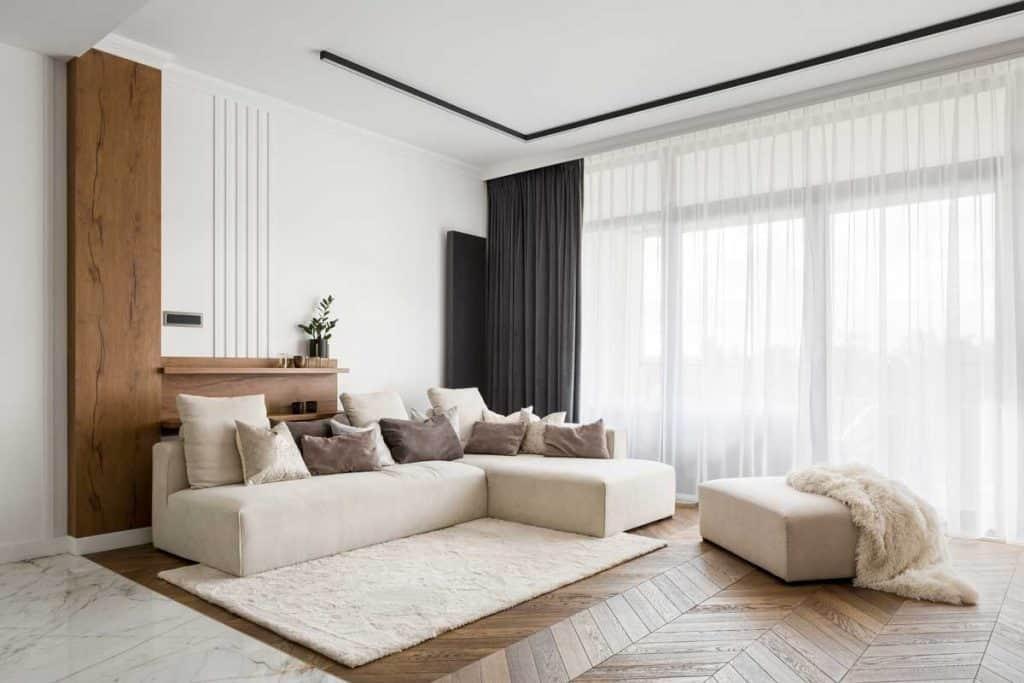 Elegant and comfortable designed living room with big corner sofa, wooden floor and big windows