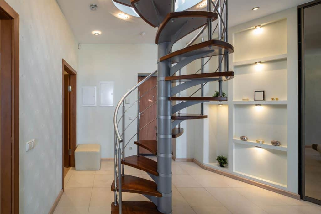 Entrance door and hall in luxury apartment. Spiral staircase. Modern interior in light tones.