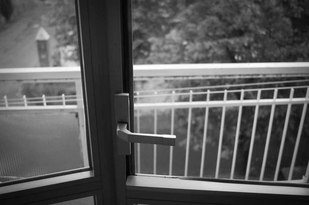 French door opens onto a balcony of an high floor building