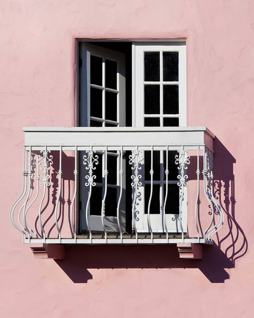 French doors open onto a white balcony, set in a pink plaster wall