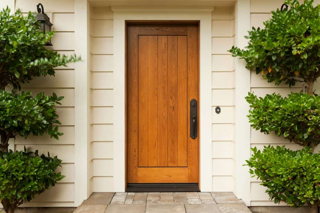 Front door of a house made from hardwood and a metal door knob