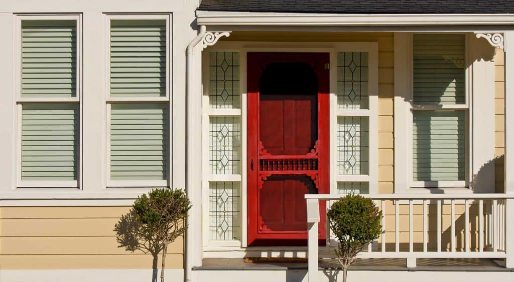 Front porch of a Victorian house with red door