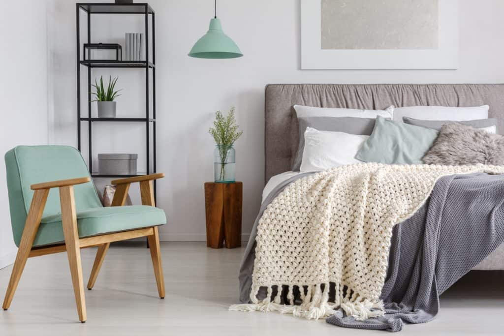 Gorgeous bedroom with blankets all over the bed and a small chair on the side