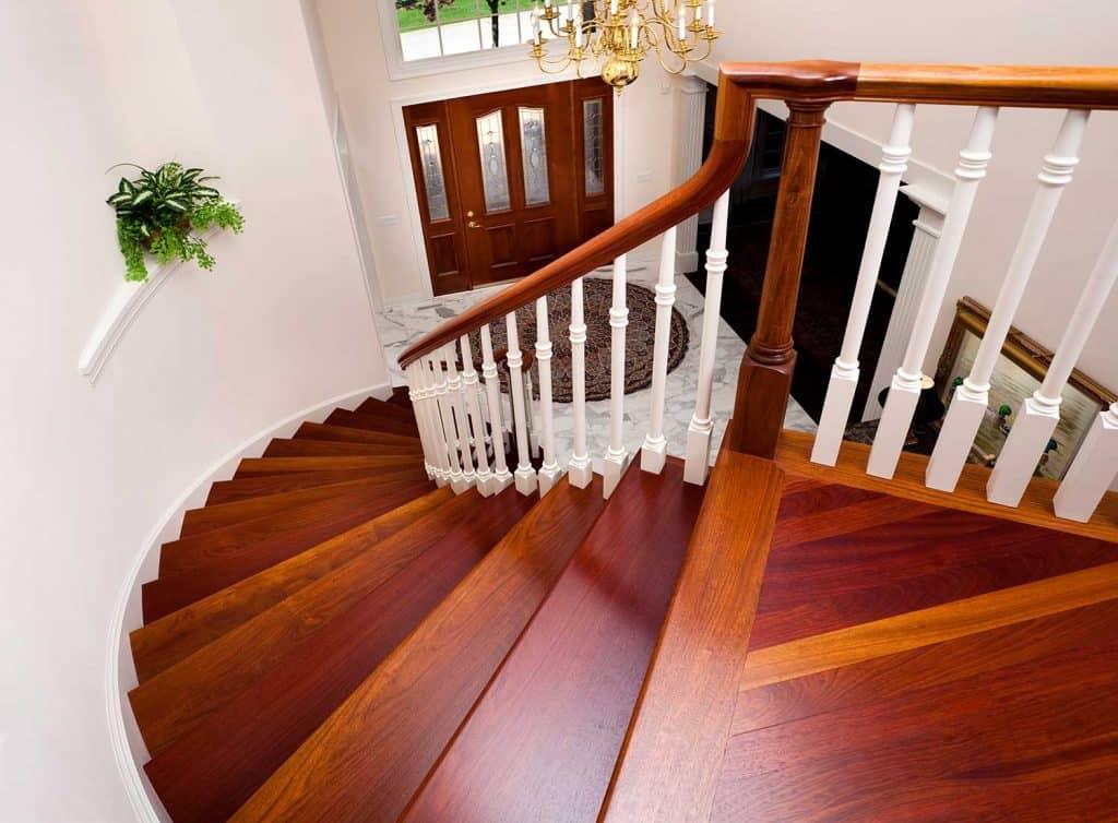 Grand foyer down beautiful winding hardwood staircase in showcase home