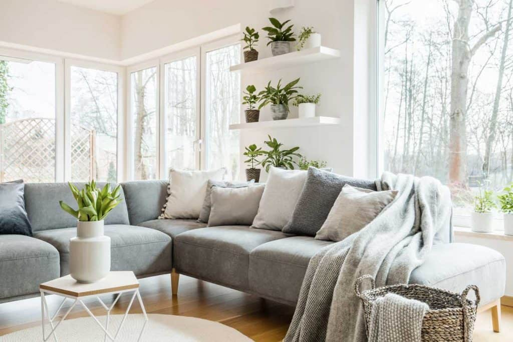 Gray corner couch with pillows and blankets in white living room interior with windows and glass door