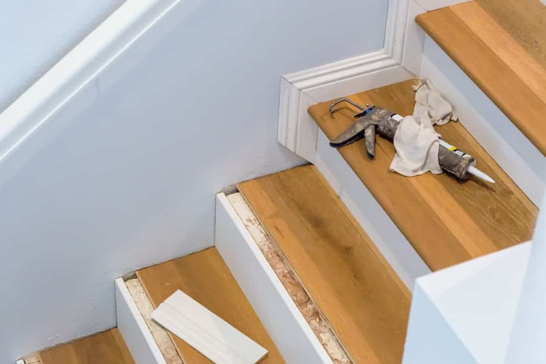 Hardwood Floor Installation On Stairs, Caulking Gun On Step, Baseboards Being Measured