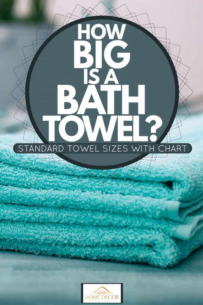 A light blue colored bath towel in a hotel room, How Big Is A Bath Towel? [Standard Towel Sizes With Chart]