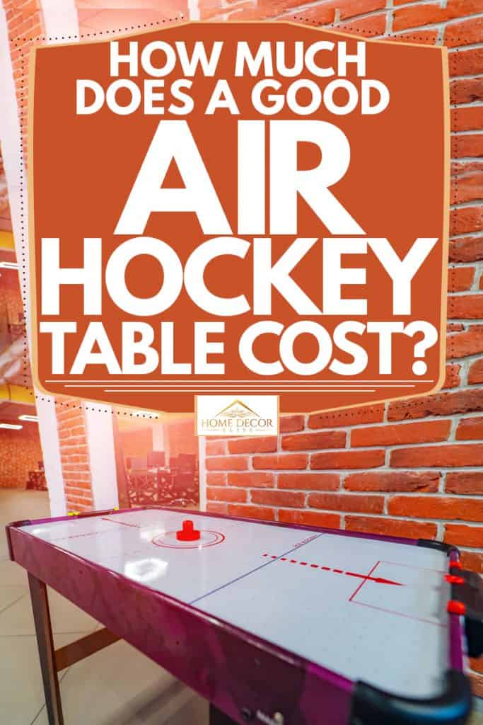 An air hockey table at an entertainment area of a house with brick walls, How Much Does a Good Air Hockey Table Cost