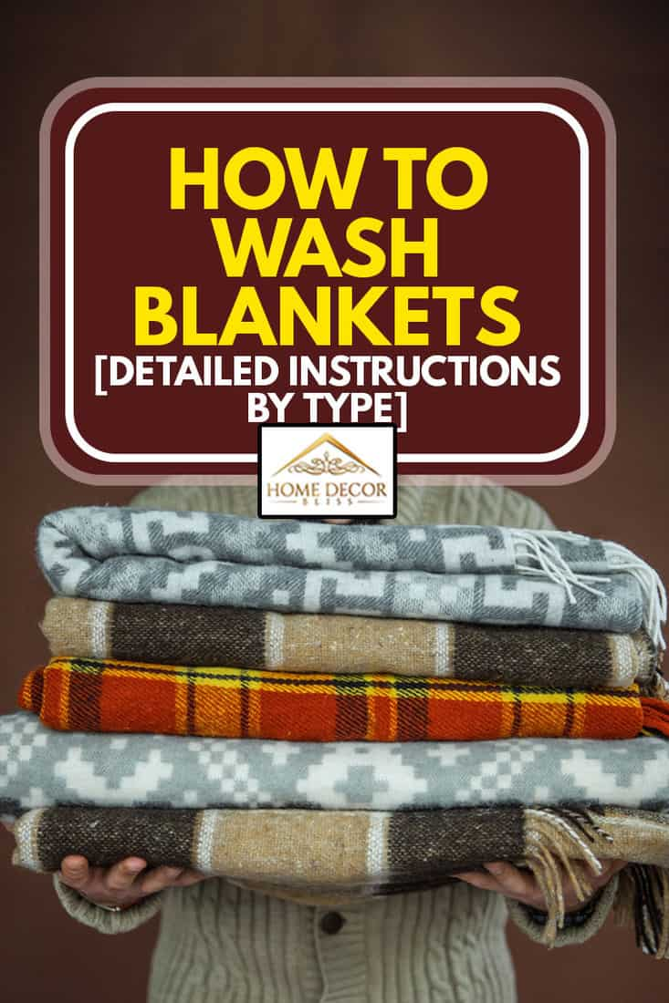 A man holding a pile of blankets, How To Wash Blankets [Detailed Instructions By Type]