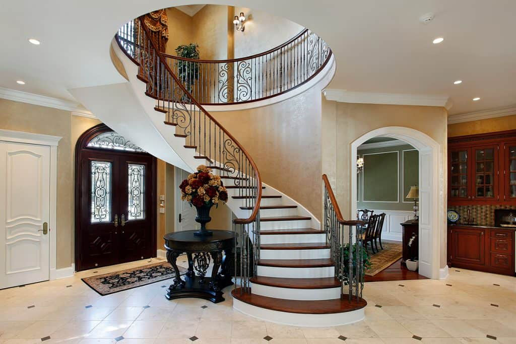 Huge mansion with a concrete staircase with a wooden stair spindle with wooden step