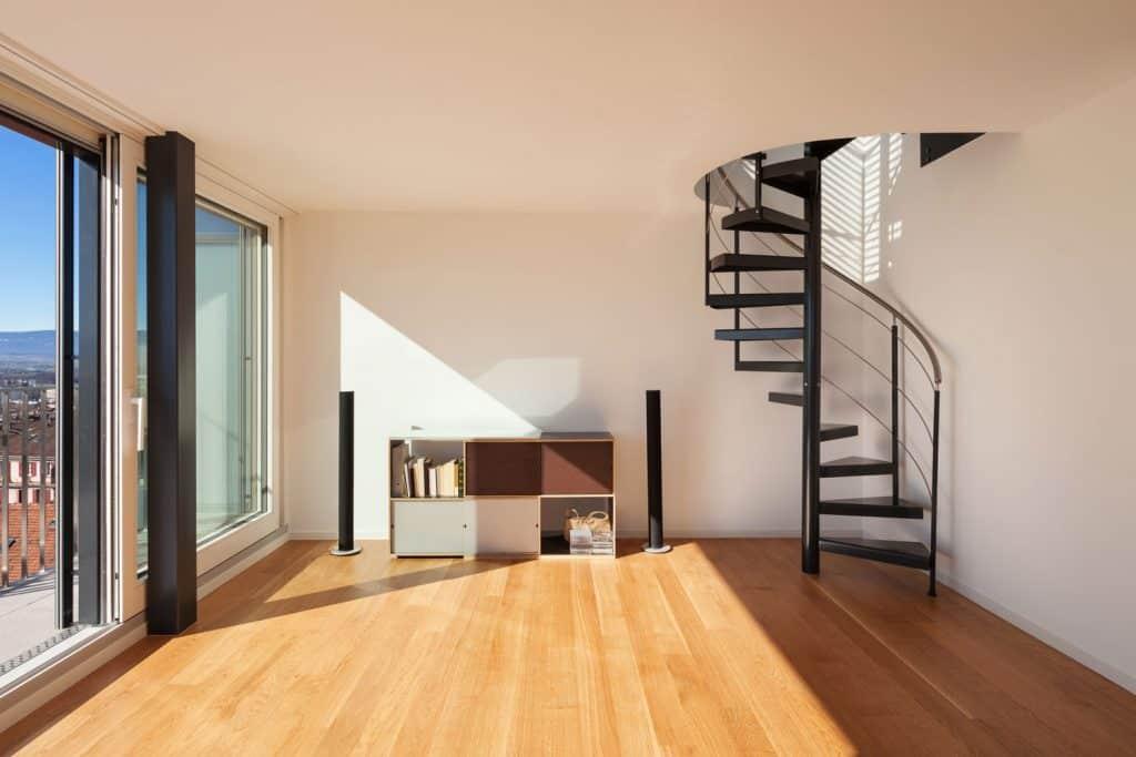 Interior, wide open space of a duplex, parquet floor, dark spiral staircase